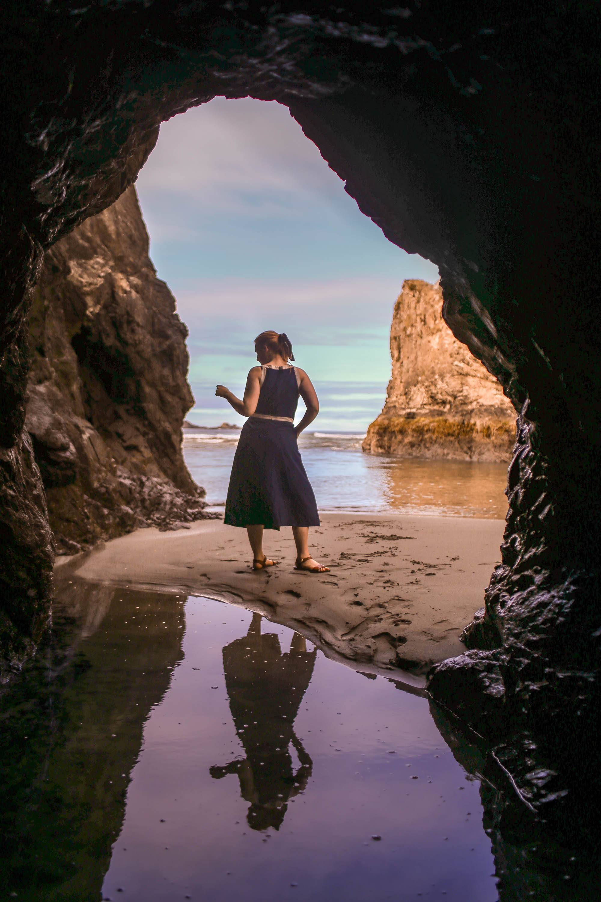 Woman in blue dress standing on beach through cave opening
