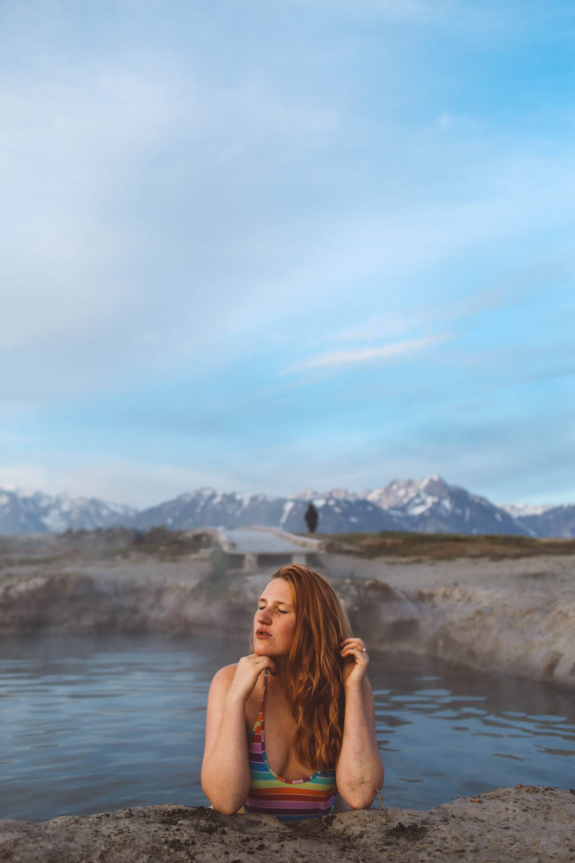 woman in a rainbow swimsuit in a hot spring in the mountains