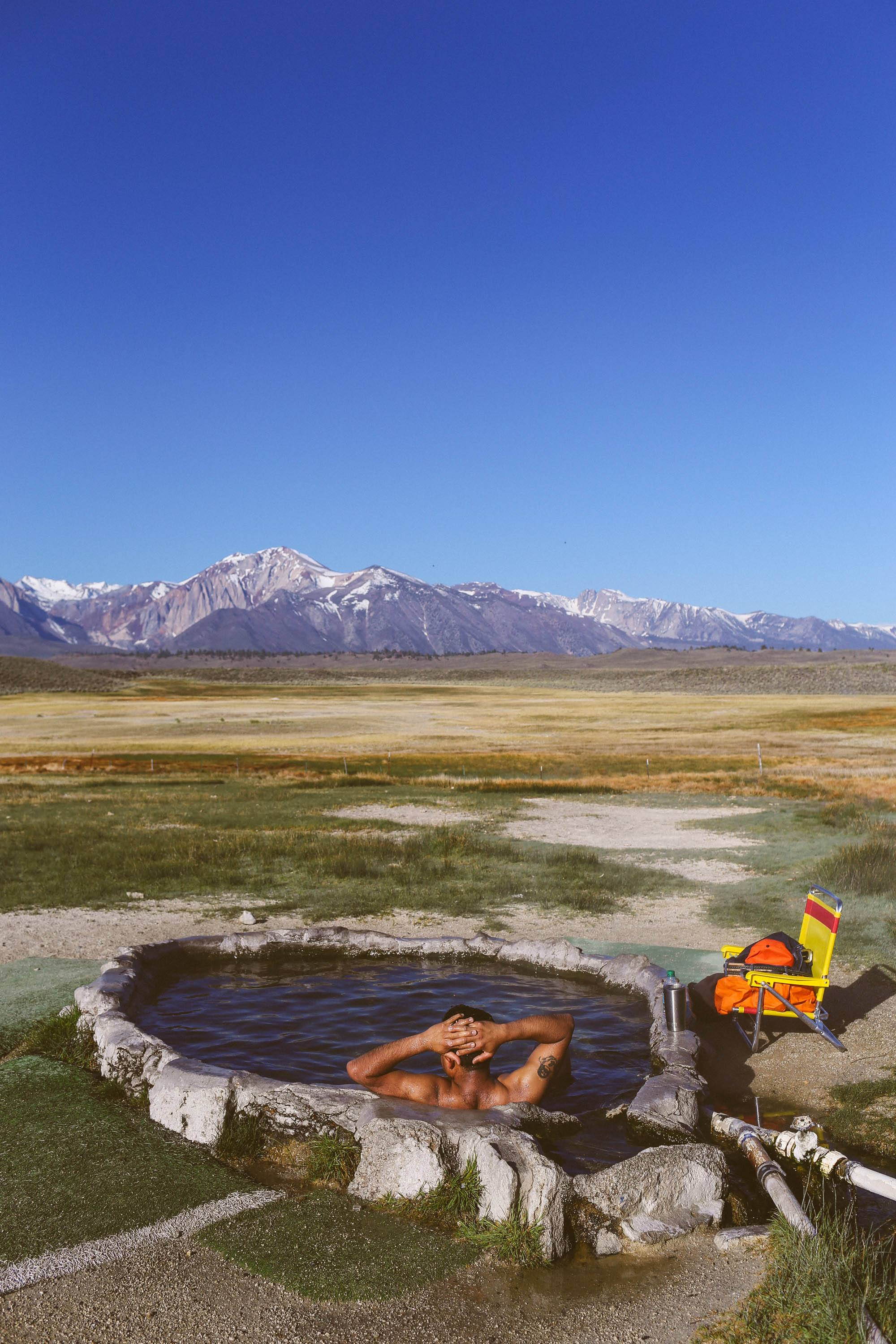 man in hot spring looking out over the plains, mountains in the background