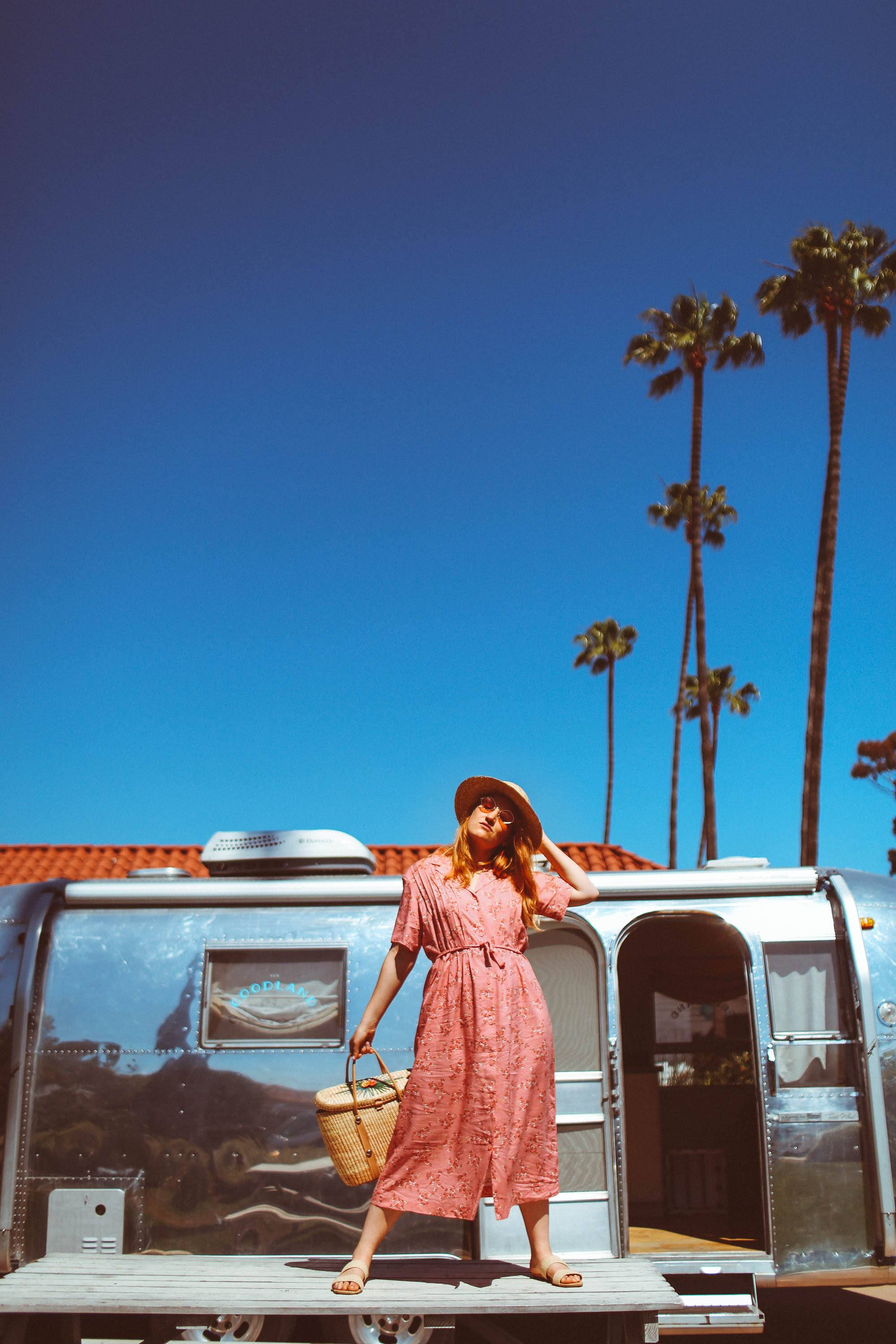 Woman in hat and vintage pink dress and hat standing on a table in front of an airstream with palm trees in the background
