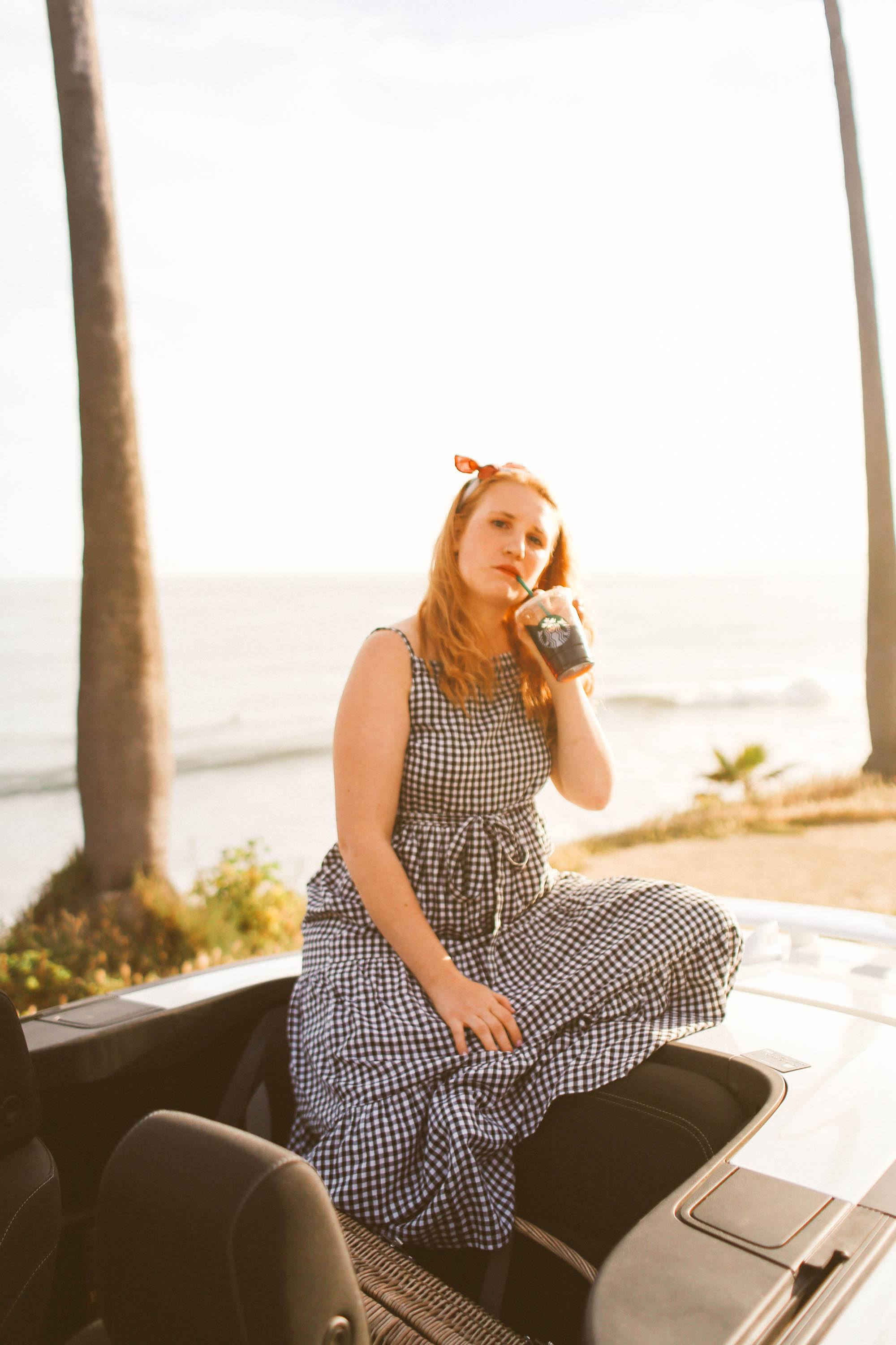 Woman in black and white gingham dress sitting on convertible drinking starbucks